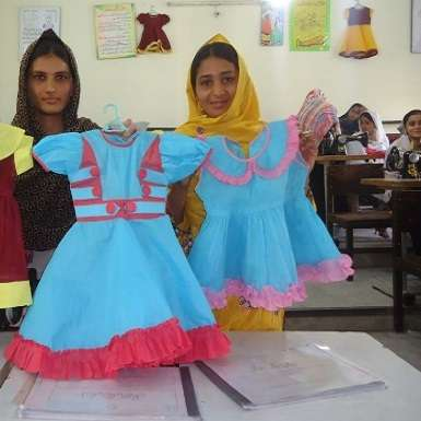 Sadia* holding dresses that she has made to sell